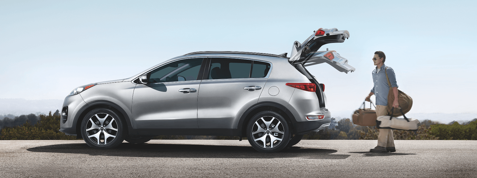 A man carrying bags, and putting them into the opening trunk of his 2019 Kia Sportage