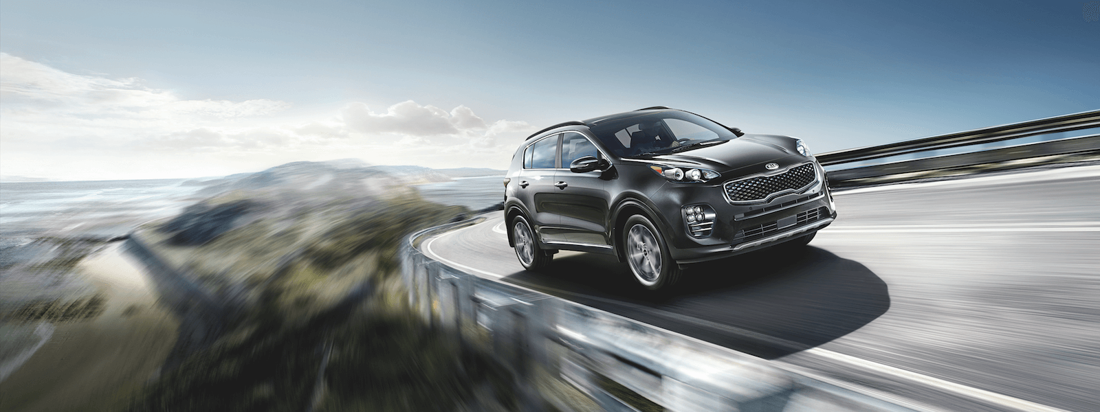 A 2019 Kia Sportage driving on a highway through the mountains