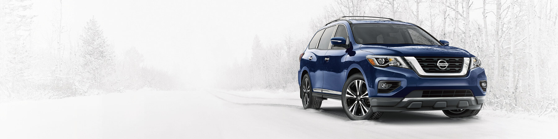 A blue 2018 Nissan Pathfinder driving in the snow
