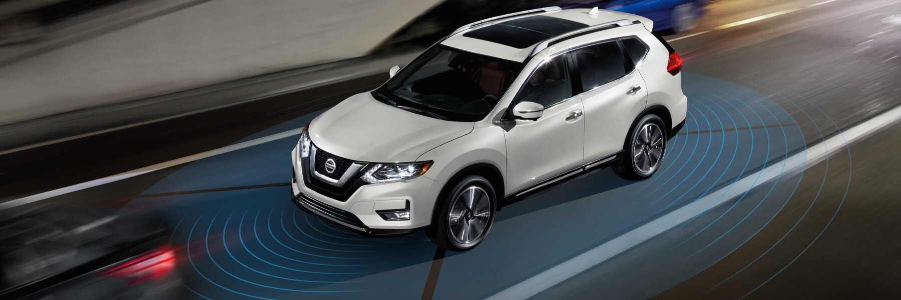 A white Nissan Rogue driving down a road using a safety sensing feature
