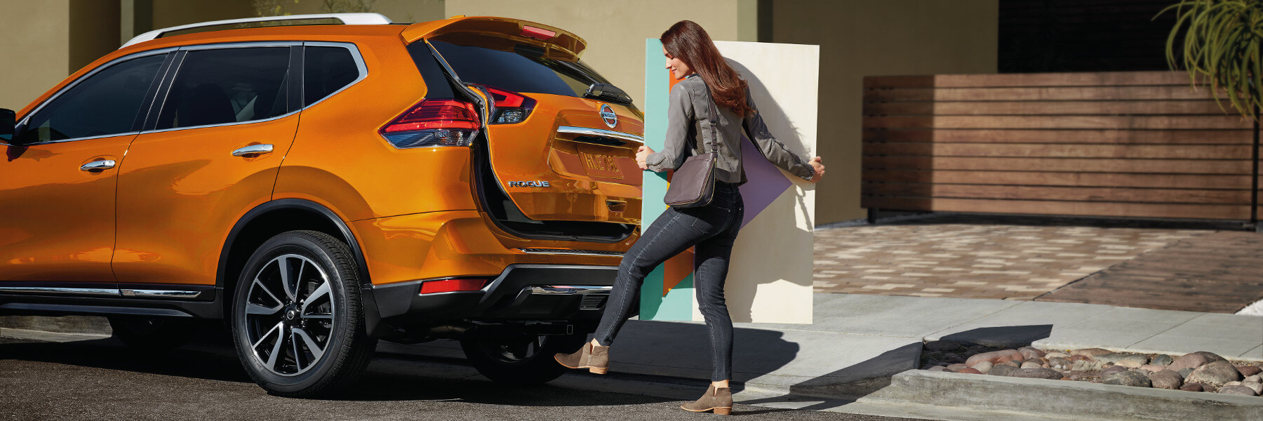 A woman holding a painting using her foot to open the back hatch on the 2018 Rogue Sport