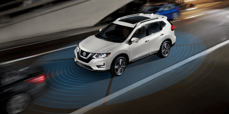A white Nissan Rogue driving down a busy street using safety features