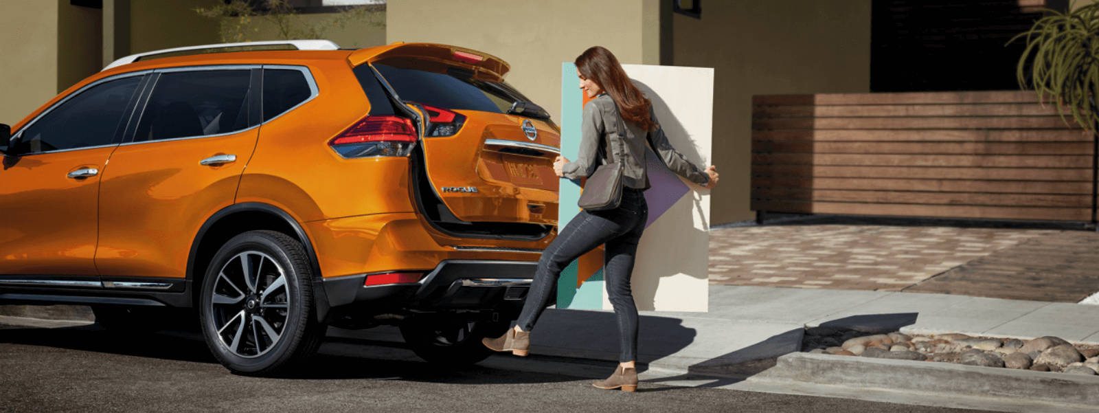 A woman putting a piece of art in the back of the trunk of her Nissan Rogue