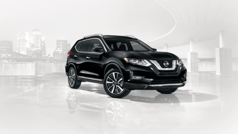 A black Nissan Rogue in front of a faded city skyline and highway