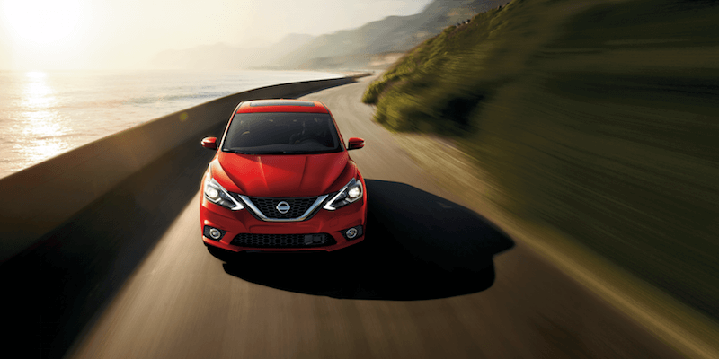 A red Nissan Sentra driving down a highway between the mountains and an ocean