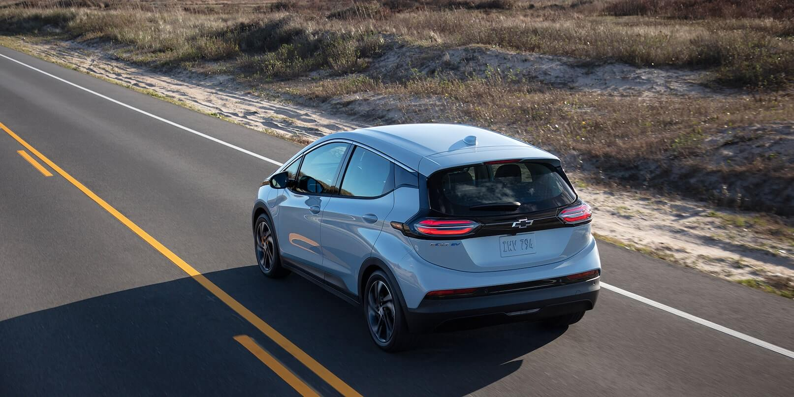 Left-rear side exterior view of the 2022 Chevrolet Bolt EV driving on the road.