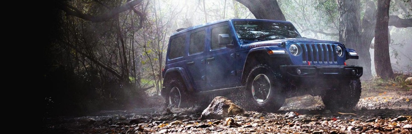 2020 Jeep Wrangler exterior shot with blue paint color driving through a forest ground of fall leaves as sun shines through the trees
