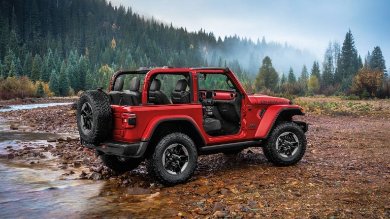 2020 Jeep Wrangler winnnipeg mb exterior side shot with firecracker red paint color and doors removed on wet earth and wood chips near a lake and forest with a foggy sky