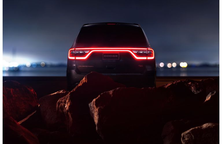 2020 Dodge Durango RT winnipeg mb exterior rear shot with LED taillight strip let up in red and framed by a mass of red rocks and stone