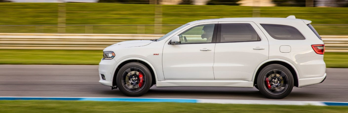 2020 Dodge Durango SRT winnipeg mb exterior side shot with white paint color and red accents as it drives around a racetrack near grass fields
