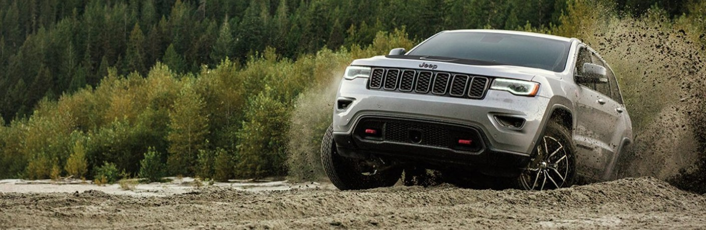 2020 Jeep Grand Cherokee Trailhawk exterior shot driving through mounds of wet dirt near a big pine tree forest