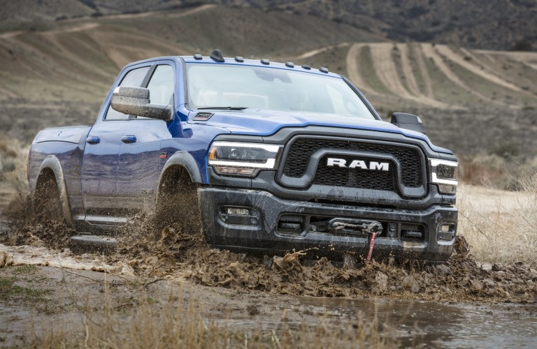 2020 Ram 2500 Power Wagon heavy-duty truck model exterior shot with blue paint color driving through mud