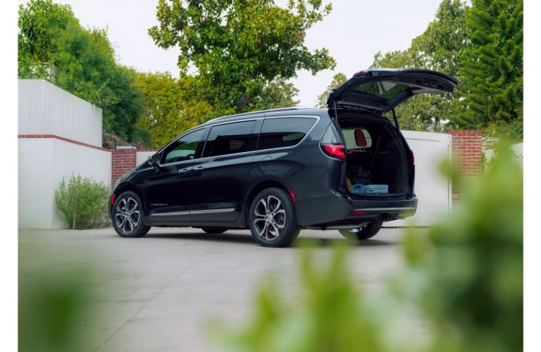 2021 Chrysler Pacifica exterior side rea shot by a brick and fence gate with trunk open for cargo loading