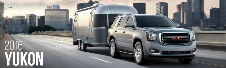 2016 GMC Yukon hauling a camper by a city