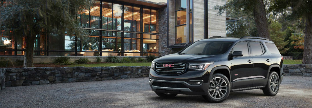 black 2017 GMC Acadia midsize SUV parked in front of a building with a big glass window
