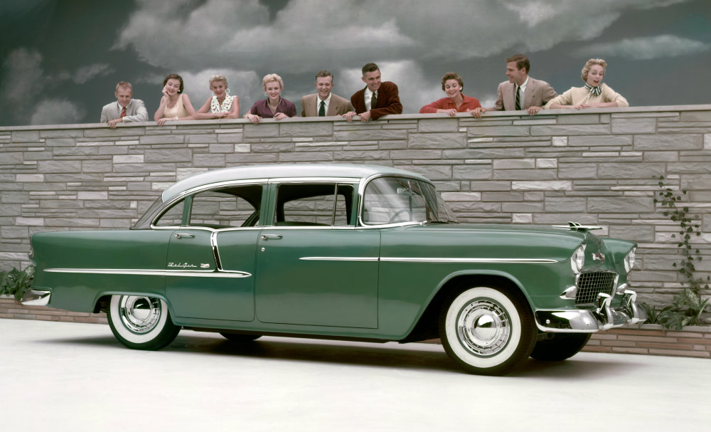 green 1955 Chevy Bel Air Sport Coupe being admired over a wall