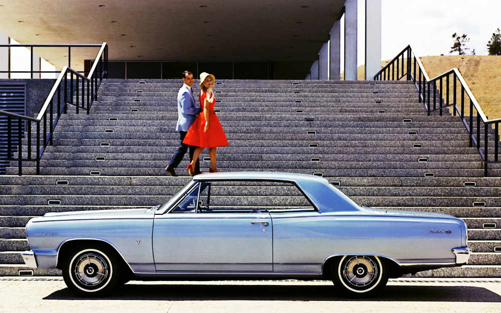 A man and a woman on stairs behind a 1964 Chevy Chevelle Malibu