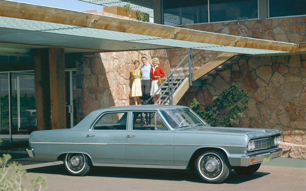 People posed behind a 1964 Chevy Chevelle Malibu by a futuristic house