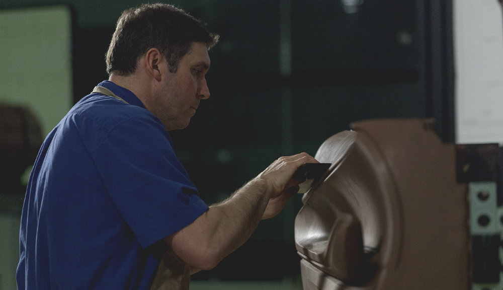 man sculpting a car's interior in clay