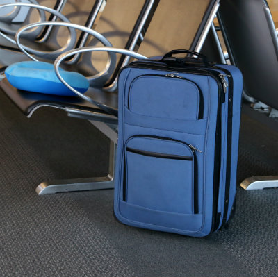 blue suitcase in a transport station signifying people on the move