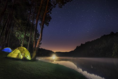 tent on the side of a lake in the dark of night