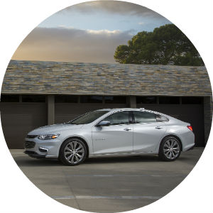 a white Chevy sedan against the background of a darker garage door