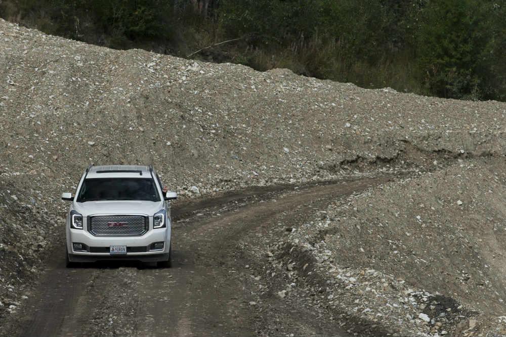 White 2015 GMC Yukon travels down a gravel path in the Yukon