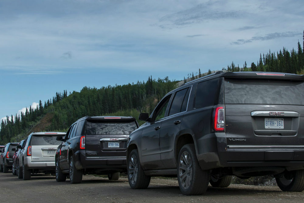 A line of 2015 GMC Yukon full-size SUV's on a gravel track in the Yukon