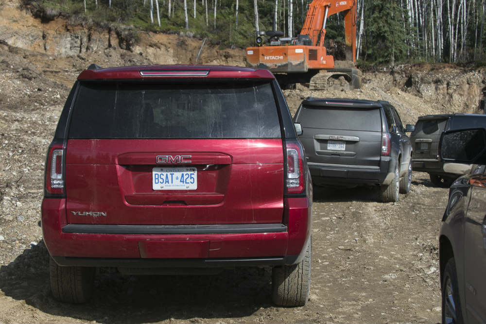 Various models of the 2015 GMC Yukon caravan through a Yukon worksite to test their mettle