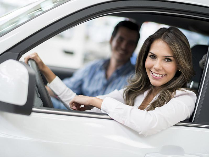 Woman looking out the window of her new vehicle