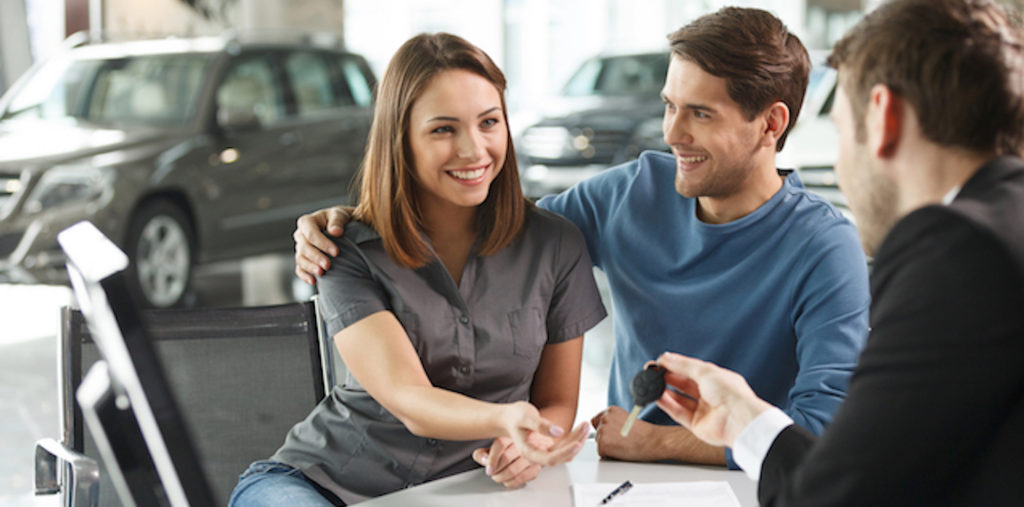 car salesman handing car keys over to young couple