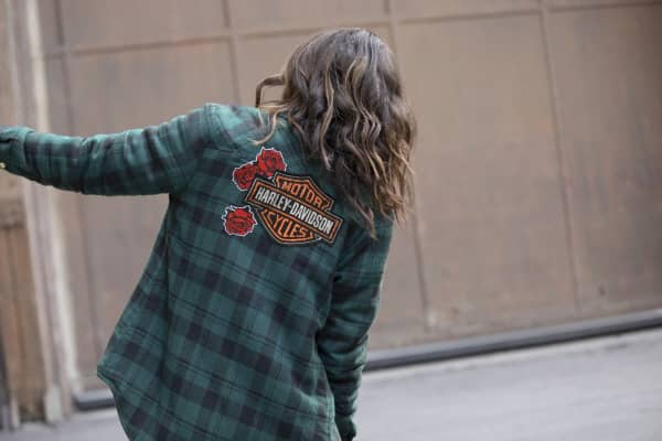 A women facing away with long, brown, wavy hair leans to the right wearing a green plaid Harley-Davidson long sleeve flannel shirt from the Harley-Davidson Garage collection.