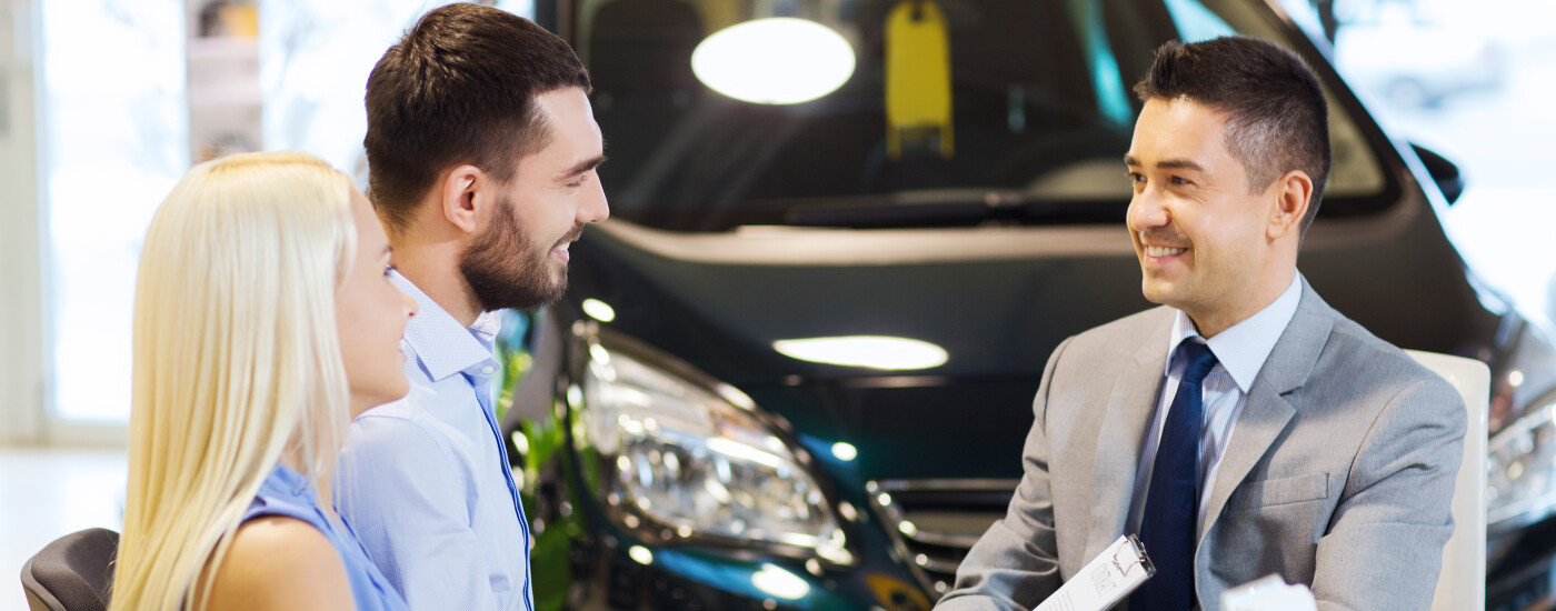 Couple sitting at sales desk at dealership
