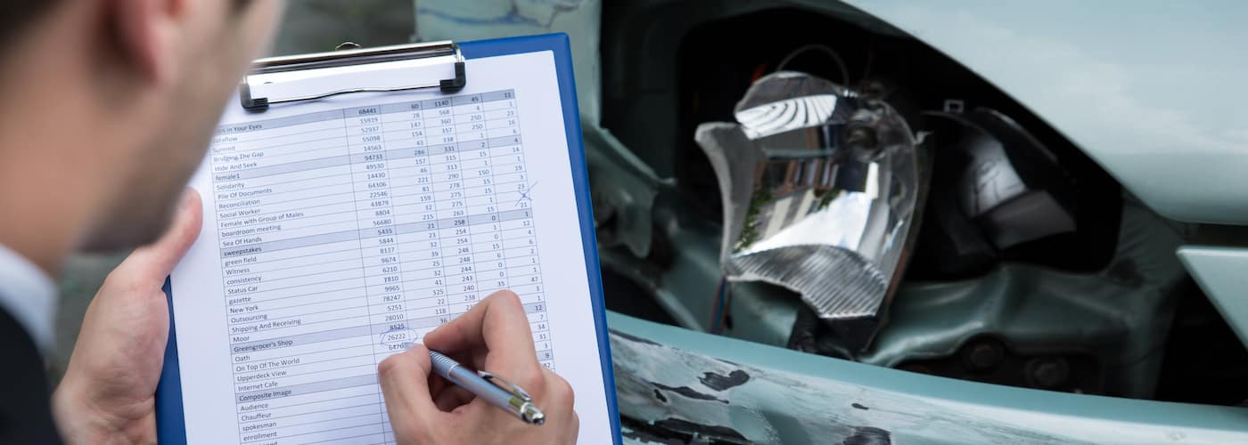 insurance agent marking damage report close up of clipboard and headlight damage