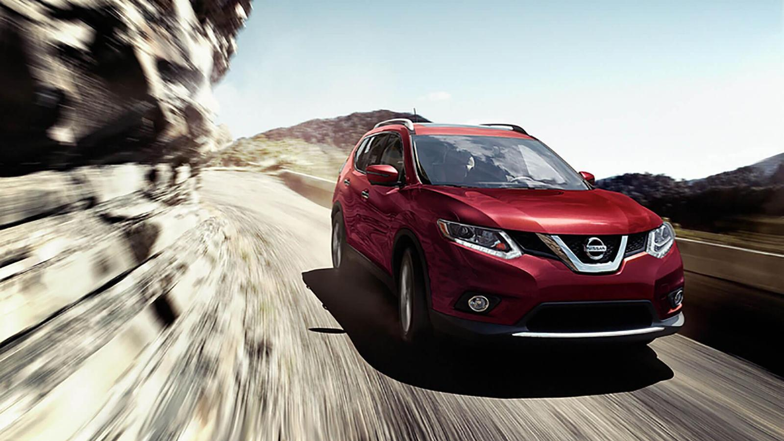 Red Nissan Rouge Driving down a mountainous road