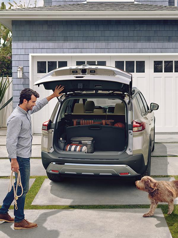 A man loading his dog into the back of his silver Nissan Rogue parked in the driveway.