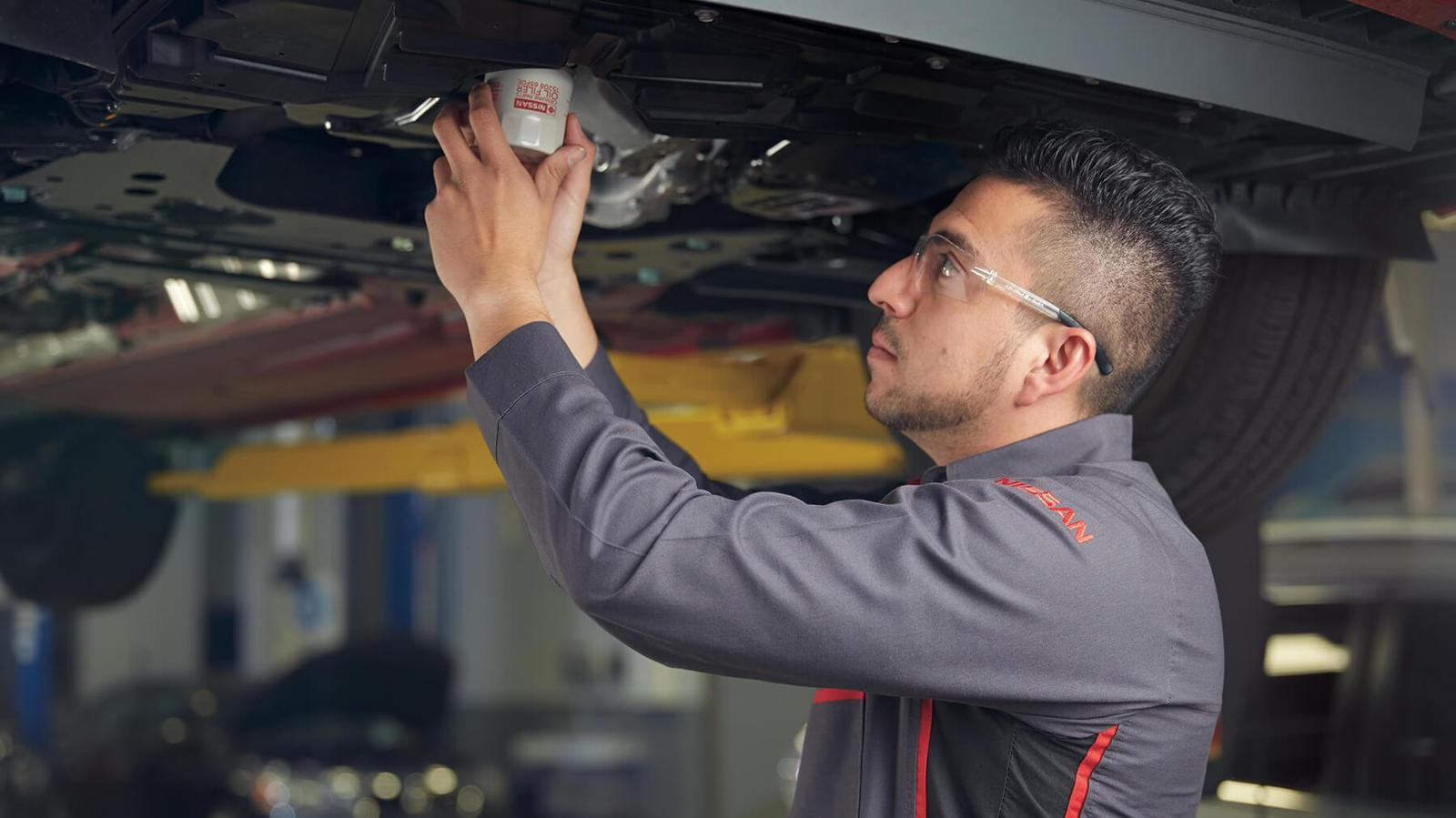 Nissan Technician Changing the Filter on Vehicle