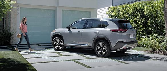 A woman walking towards her grey Nissan Rogue parked in the driveway.