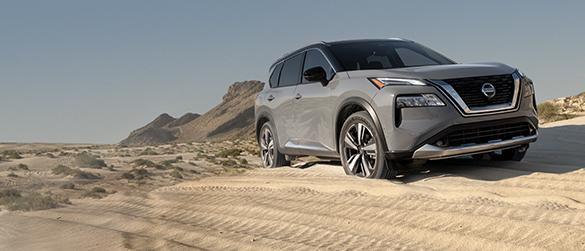 A grey Nissan Rogue driving off-road in the desert.