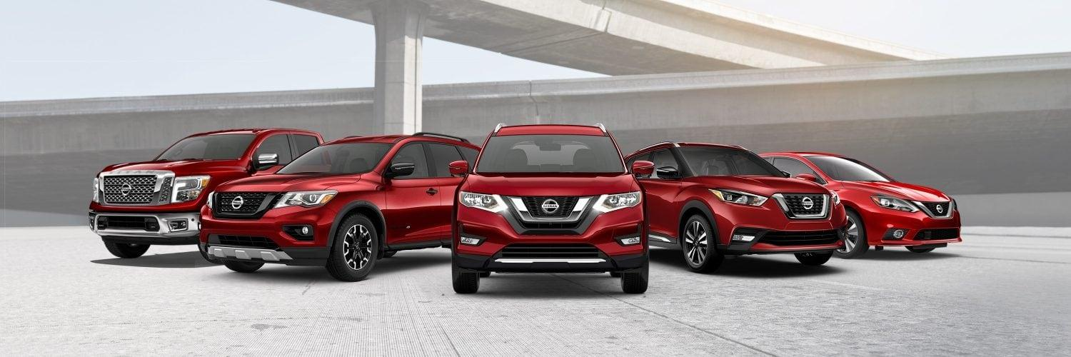 Lineup of Nissan vehicles in red with a highway overpass in the background.