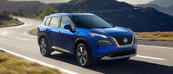 A blue Nissan Rogue driving down a curvy highway.