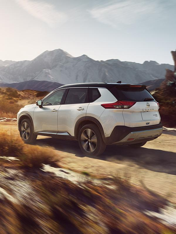 A white Nissan Rogue driving along a desert dirt road.
