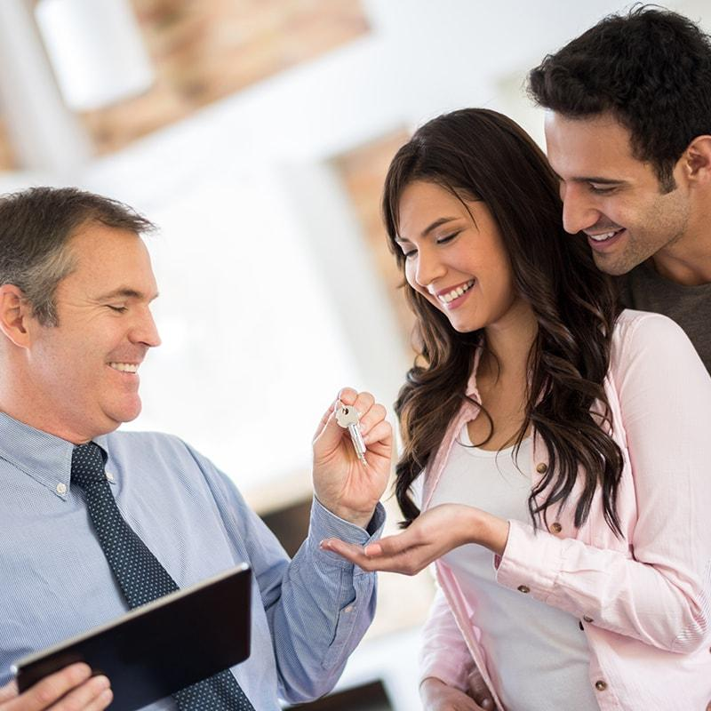 Salesman handing a happy couple their new car keys