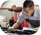 Toyota technician inspecting an engine